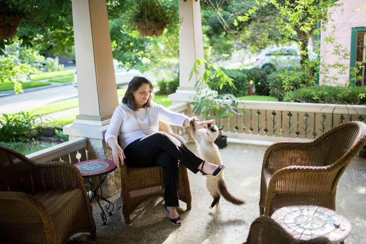 Kathleen English pets her cat Dante at her porch, Wednesday, May 30, 2018, in Houston. English built a certified wildlife habitat in her front and back yard in 2011. ( Marie D. De Jesus / Houston Chronicle )