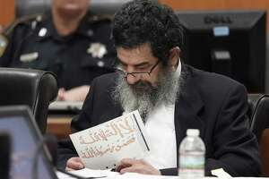 """Ali Mahwood-Awad Irsan is shown in court Monday, June 25, 2018 in Houston holding a paper written in Arabic and colored with orange marker of the mantra, """"There is no god but God and Mohammad is God's Prophet."""" Irsan was charged with capital murder because his alleged crime involved multiple victims — his daughter's best friend, Gelareh Bagherzadeh, an Iranian medical student and activist, and his daughter's husband, Coty Beavers, 28. Both slayings, authorities said, were driven by the anger of Irsan, a conservative Muslim, over his daughter Nesreen's decision to marry Beavers, a Christian from Houston. ( Melissa Phillip / Houston Chronicle )"""