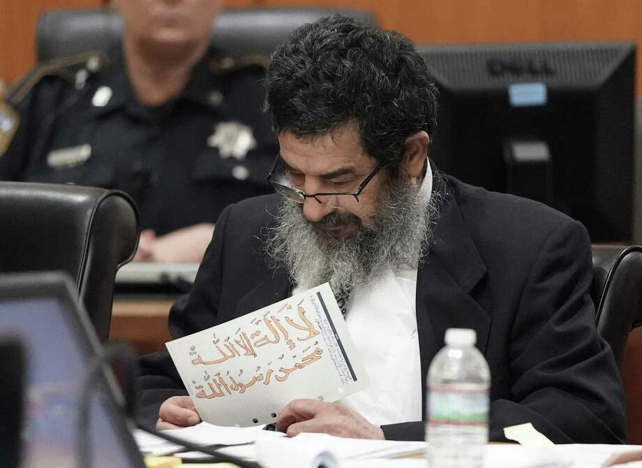 """Ali Mahwood-Awad Irsan is shown in court Monday, June 25, 2018 in Houston holding a paper written in Arabic and colored with orange marker of the mantra, """"There is no god but God and Mohammad is God's Prophet."""" Irsan was charged with capital murder because his alleged crime involved multiple victims — his daughter's best friend, Gelareh Bagherzadeh, an Iranian medical student and activist, and his daughter's husband, Coty Beavers, 28. Both slayings, authorities said, were driven by the anger of Irsan, a conservative Muslim, over his daughter Nesreen's decision to marry Beavers, a Christian from Houston. ( Melissa Phillip / Houston Chronicle ) Photo: Melissa Phillip, Staff / Houston Chronicle / © 2018 Houston Chronicle"""