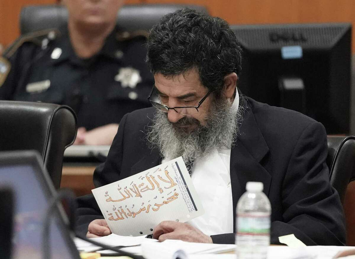 Ali Mahwood-Awad Irsan is shown in court Monday, June 25, 2018 in Houston holding a paper written in Arabic and colored with orange marker of the mantra, ?