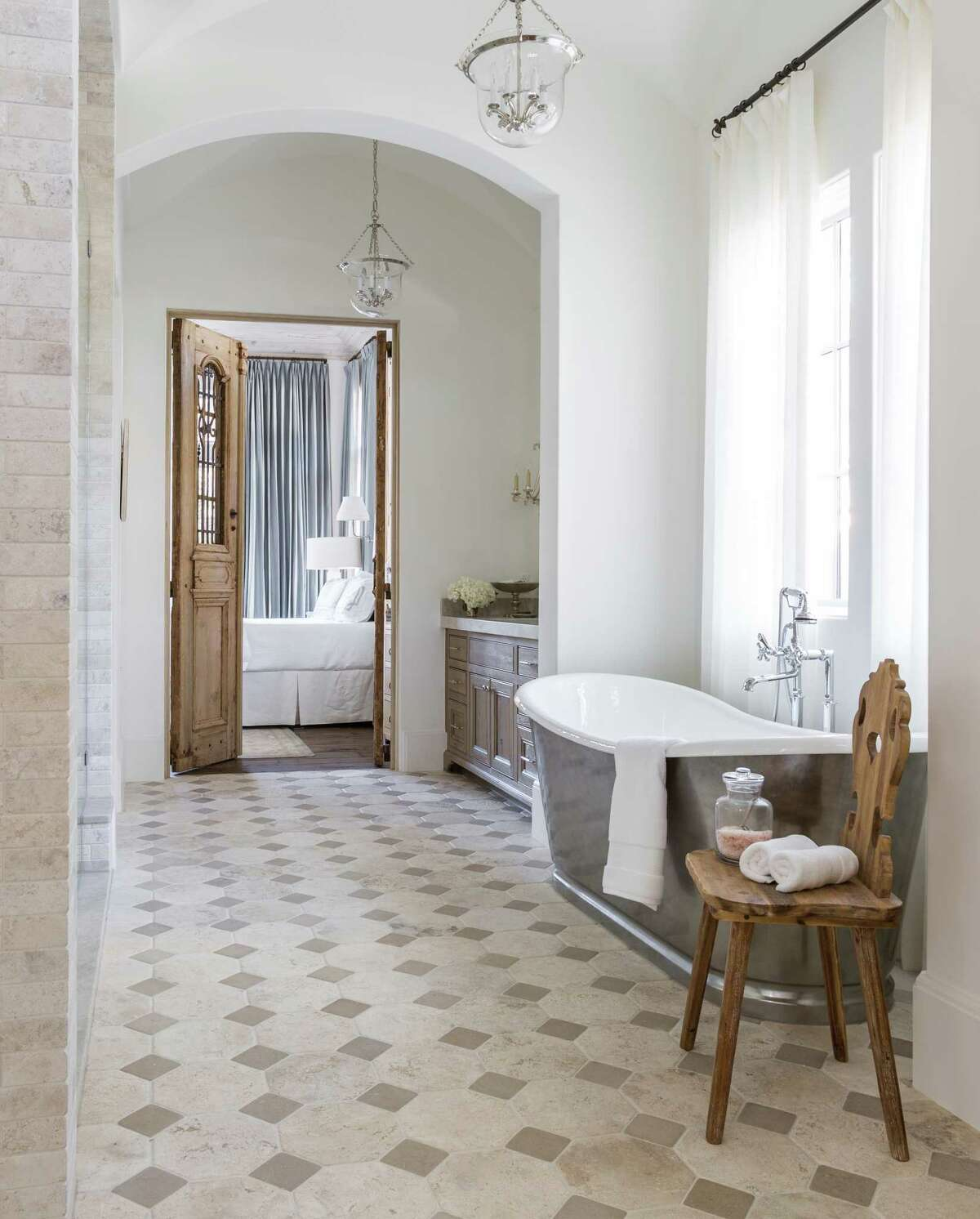 In the master bath, an antique chair from Lam Bespoke sidles up to a Penhaglion steel-wrapped soaking tub.