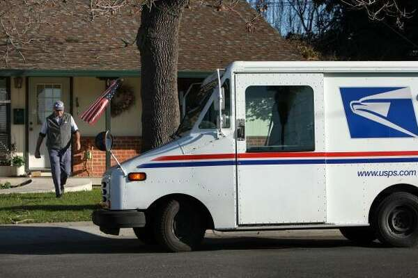 A U.S. Postal Service letter carrier walks back to his truck after delivering a package.