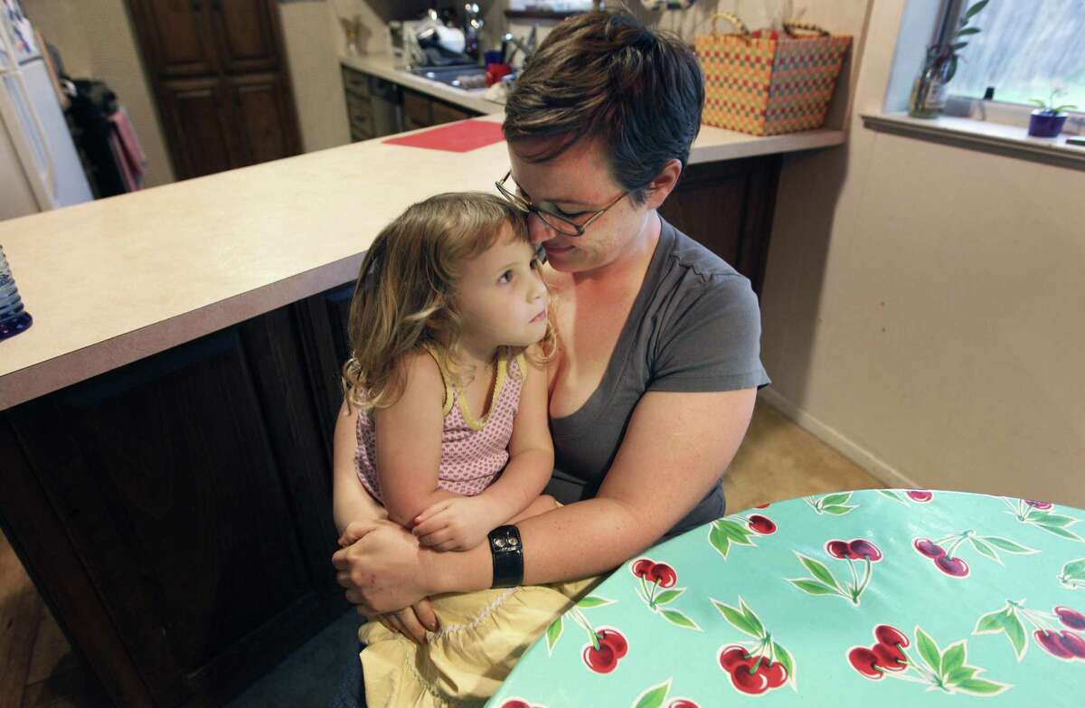In this March 8, 2012 photo, Alexis Lohse, right, hugs her daughter Emma Miller, 3, at their home in Fort Worth, Texas. When Lohse decided to go back to college, the mother of two was so worried about health insurance that she didn't quit her job until finding the Women's Health Program. Texas Gov. Rick Perry is directing state officials to begin looking for money to keep the Medicaid Women's Health Program operating, even if the Obama administration revokes federal funding amid a fight over clinics affiliated with abortion providers. (AP Photo/LM Otero)