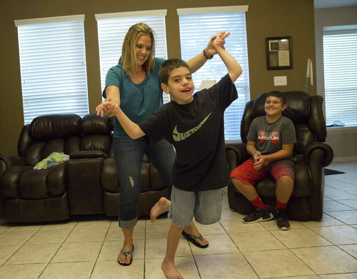 Nicholas Cantu, 9, gets assist from his mother to make a whip dance move at home Friday, June 30, 2017, in Spring. Nicholas has significant disabilities after being born premature and his parents are worried that potential reductions to Texas for Medicaid as part of the Senate's bill to repeal and replace the Affordable care Act will chip away at the day to day services they need to not only keep Nicholas alive but also help them manage his care. ( Yi-Chin Lee / Houston Chronicle )
