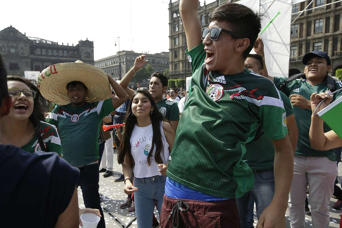 Mexico fans celebrate at the end of the World Cup group F match between Germany and Korea, in Mexico City's main square, the Zocalo, Wednesday, June 27, 2018. Mexico lost the match but was able to advance to the next round because Korea knocked Germany out of the tournament. (AP Photo/Moises Castillo)