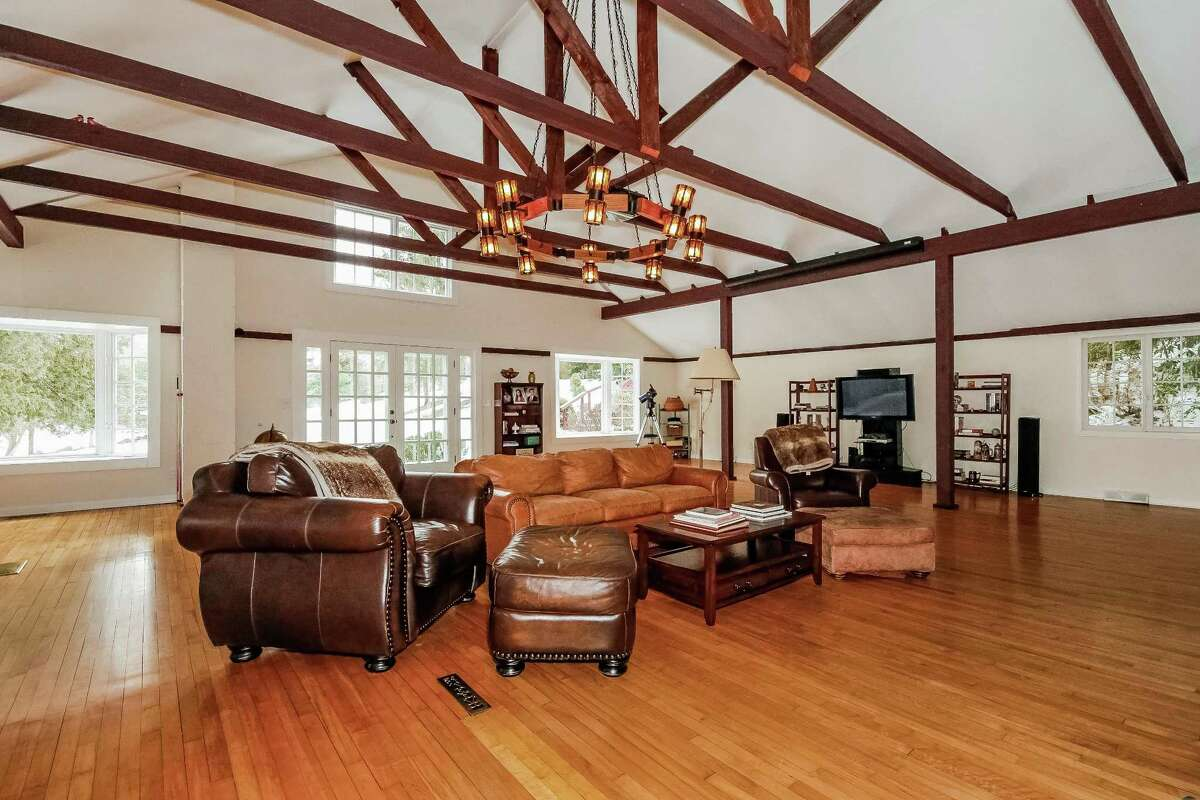 The cavernous great room features exposed, reclaimed trestle beams, bay windows, a large fireplace, and French doors to the wood deck.