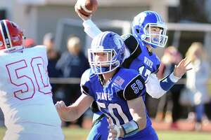 At right, Darien quarterback Peter Graham throws during the 2017 Turkey Bowl high school football game between Darien High School and New Canaan High School at Boyle Stadium last season.