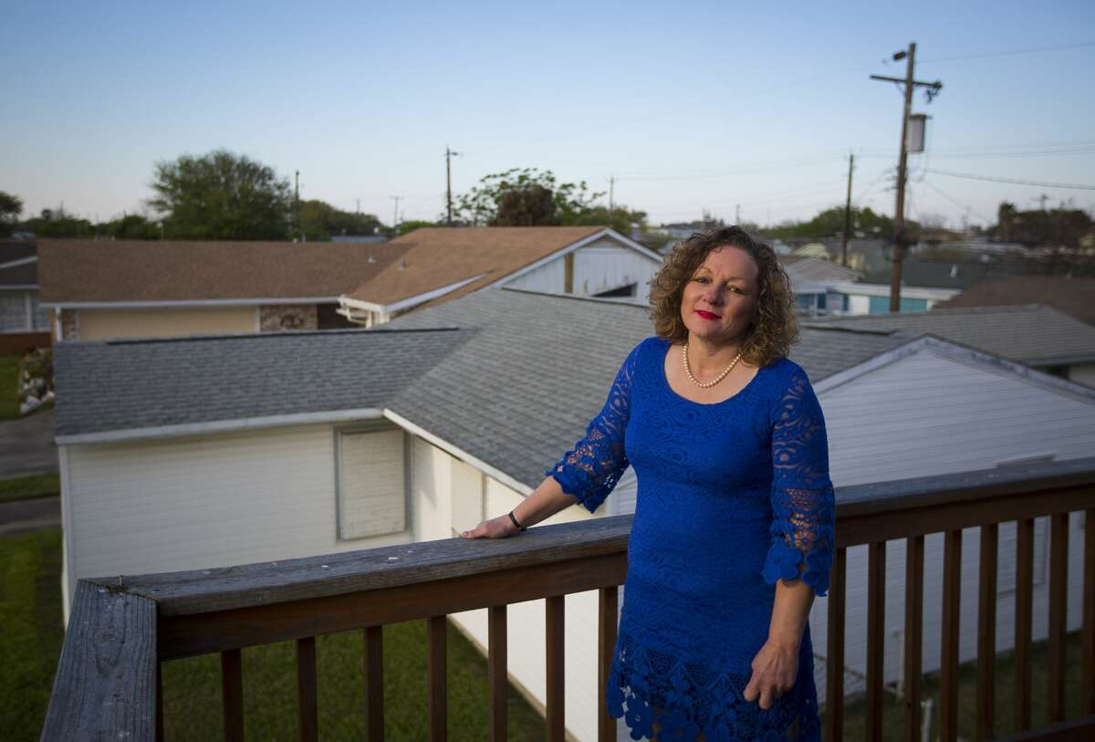 Julia Hatcher, a Galveston attorney, stands on the second floor balcony of her raised home above the non-elevated houses of her neighbors on Campbell Lane. Hatcher raised her home after it filled with six feet of water during Hurricane Ike. It still sits as one of the few raised homes on the block.
