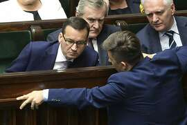 Polish Prime Minister Mateusz Morawiecki, left, talks with a lawmaker during a parliament debate on changes to the controversial Holocaust law, in Warsaw, Poland, Wednesday, June 27, 2018.  Lawmakers have passed changes to a disputed Holocaust speech law, removing criminal provisions for attributing Nazi crimes to Poles. Next to Morawiecki are deputy prime ministers Piotr Glinski, center and Jaroslaw Gowin. (AP Photo/Alik Keplicz)