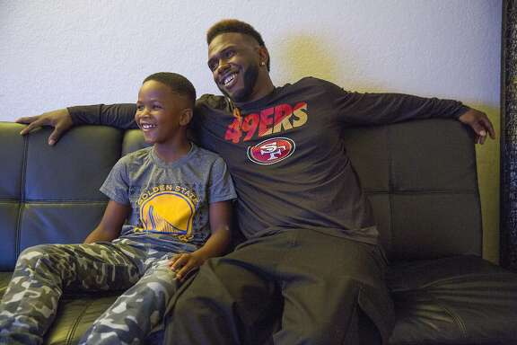 From left: Jamahl Mackey and his father Jamahl watch the television at their home on Thursday, Sept. 28, 2017, in Sacramento, Calif. The two were formerly homeless in San Francisco, where they slept in a car. They now receive support from Hamilton Families and city resources.