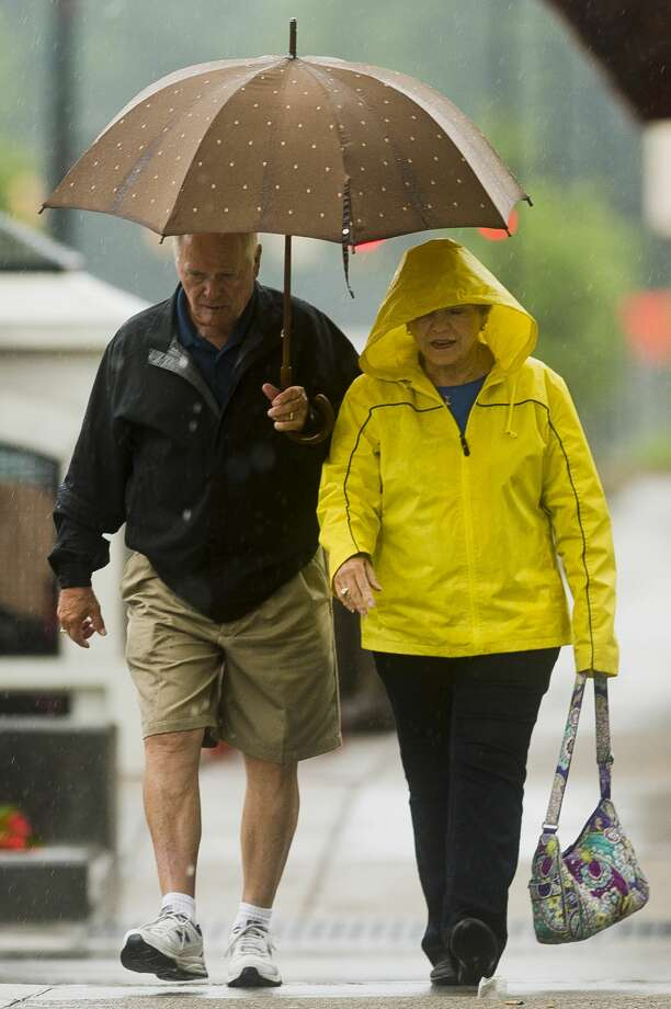 Saginaw residents Jim and Barb Leroux share an umbrella as they walk down Main Street on Wednesday, June 27, 2018. (Katy Kildee/kkildee@mdn.net) Photo: (Katy Kildee/kkildee@mdn.net)