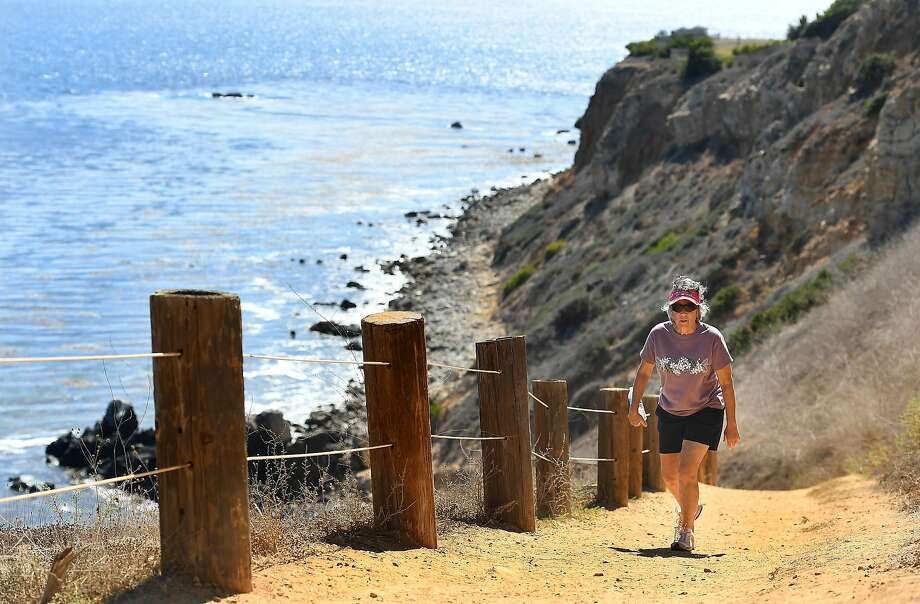 A resident walks up a hiking trail in Rancho Palos Verdes, Los Angeles County. In Southern California, cliffs could recede more than 130 feet by the year 2100 if the sea keeps rising. Photo: Wally Skalij / Tribune News Service