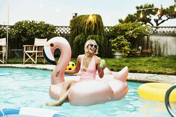 Laughing woman sitting on inflatable pool toy in backyard pool on summer evening
