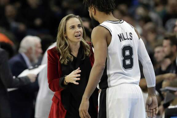 San Antonio Spurs assistant coach Becky Hammon, left, talks with guard Patty Mills (8) during the second half of an NBA basketball game against the New York Nets, in San Antonio. A diversity report released shows the NBA continues to lead the way in men's professional sports in racial and gender hiring practices.