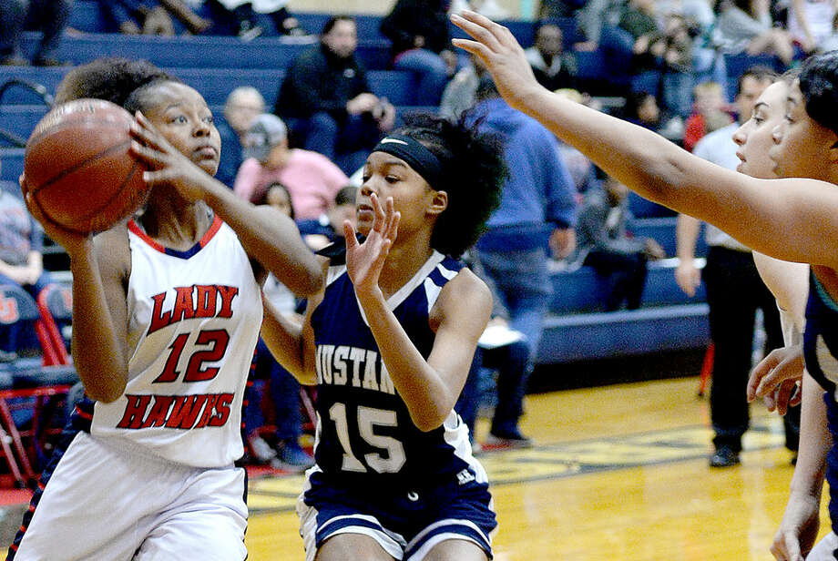 Hardin-Jefferson's Alexis Wheeler passes on the inside against the pressure of West Orange-Stark's Mar'Landria Hebert during their match-up in Sour Lake Tuesday.