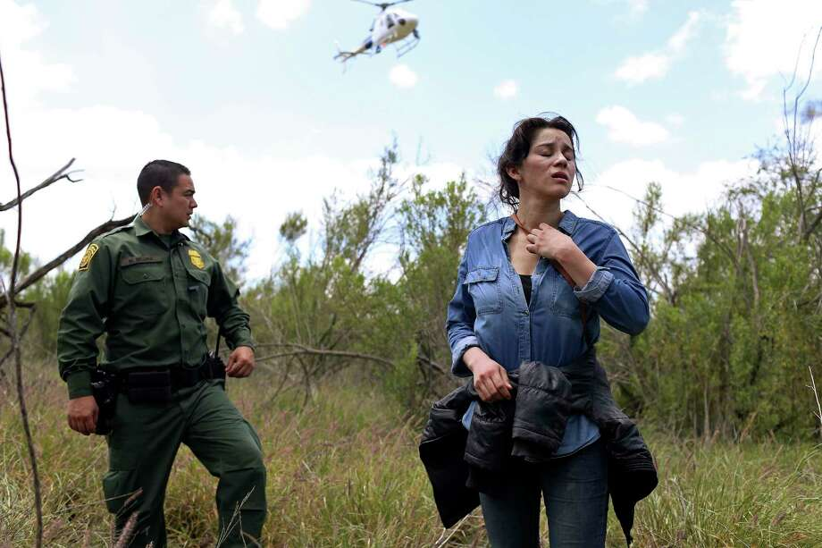 U.S. Border Patrol agent Marcelino Medina detains Veronica Reyes, 26, of Veracruz, Mexico, near the Anzalduas International Bridge in Mission, Texas, Thursday, May 10, 2018. Reyes was with a group of five immigrants attempting to enter the U.S. illegally. The rest were able to cross back into Mexico and escape detention. Photo: JERRY LARA, San Antonio Express-News / San Antonio Express-News