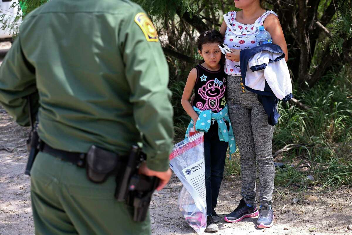 Angie Hernandez Martinez, 9, holds on to her mother, Doris Martinez, 34, after they surrendered to U.S. Border Patrol agents near the Anzalduas International Bridge in Mission, Texas, Thursday, May 10, 2018. They were one of several Honduran families that surrendered to agents that morning.