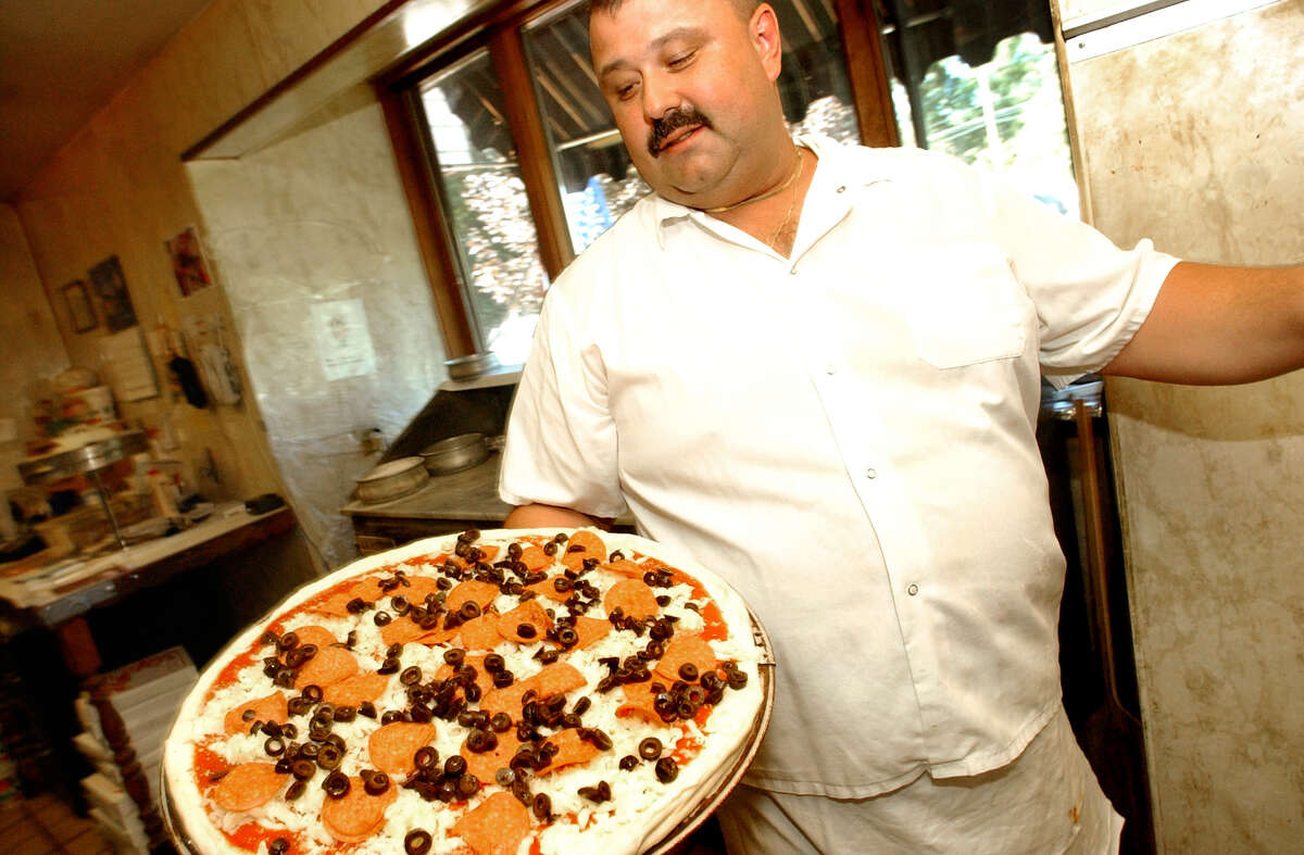 Times Union staff photo by Cindy Schultz Vince Ferretti prepares a pepperoni and olive pizza for the oven Friday, Sept. 10, 2004, at Ferretti's Family Restaurant and Pizza in Clifton Park, N.Y. He founded the restaurant with his parents in 1988.