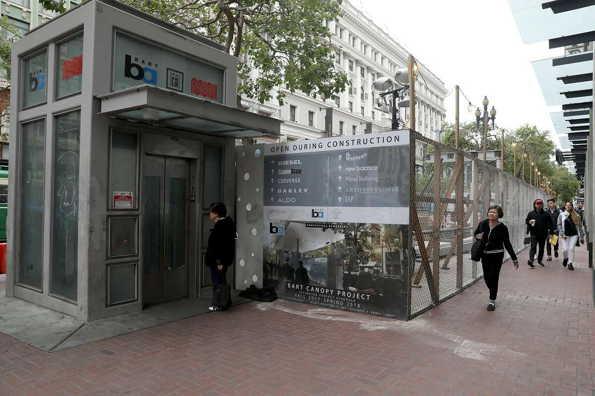 The fenced in area with pedestrians passing by is where the Bart canopy project is located on Market at Ellis streets on Wednesday, June 27, 2018 in San Francisco, Calif.