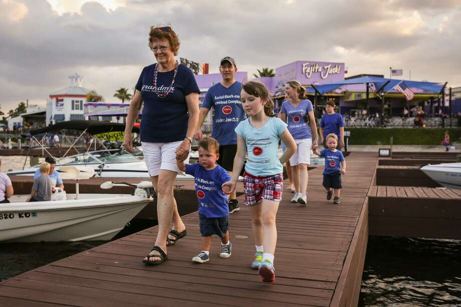 Azriel Stork, 2, center, walks along the pier in front of Fajita Jack's with his grandmother Joyce Brown and family friend Evelyn Welchel, 6, before the Fireworks Over Lake Conroe event on Tuesday, July 4, 2017. Photo: Michael Minasi, Staff Photographer / Houston Chronicle / © 2017 Houston Chronicle