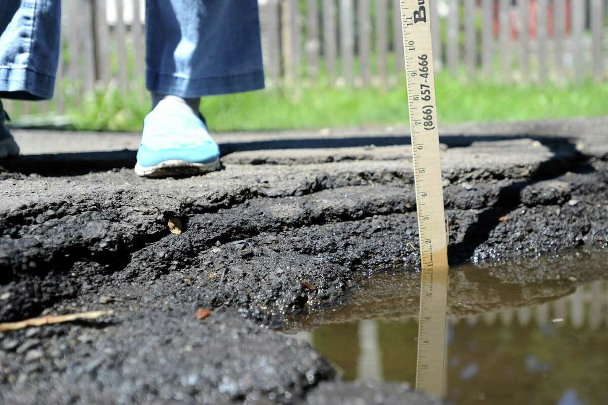 Brookside Drive resident Liberty Gilbert holds a yardstick in one of the street's deep potholes, measuring over 5 inches from the bottom, on Tuesday in Stamford.