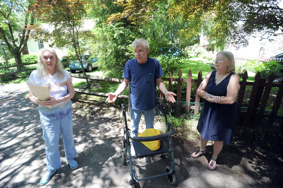 Brookside Dr. residents, from left, Liberty Gilbert, Roy Mehner and Kathy Mehner discuss the potholes covering Brookside Dr. in Stamford, Conn. on Tuesday, June 26, 2018. The problem has gotten so bad for the residents that the city will not pick up their trash, citing safety concerns for city employees.