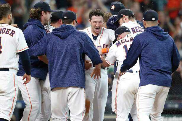 Houston Astros third baseman Alex Bregman (2) is mobbed by his teammates as they celebrate his two-run home run  in the bottom of the ninth inning at Minute Maid Park on Wednesday, June 27, 2018 in Houston. Astros won the game 7-6/
