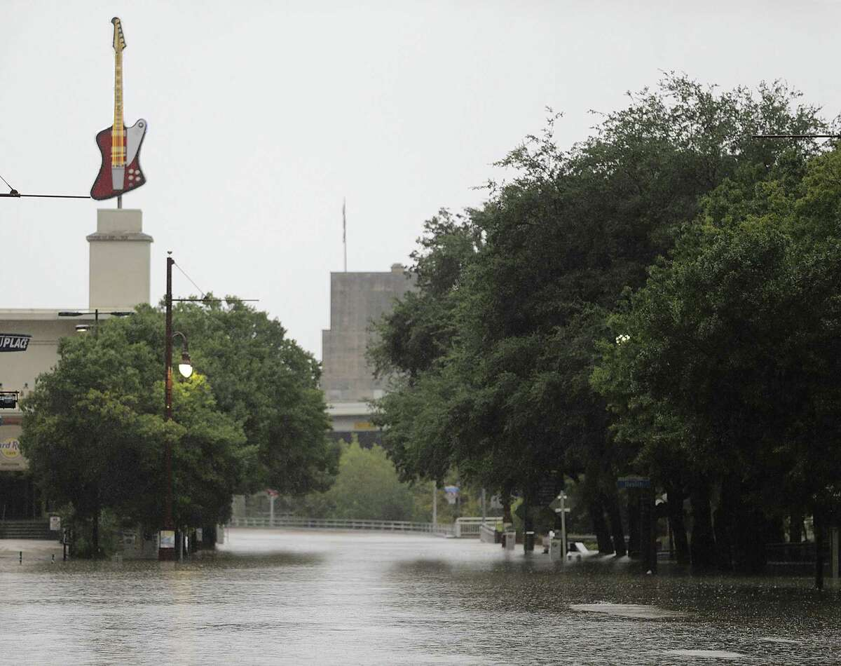 The Reisner police complex - one of many city buildings, downtown and elsewhere, that flooded during Hurricane Harvey - is visible in the background behind the flooded intersection of Texas and Smith in downtown Houston on Aug. 27, 2017. ( Elizabeth Conley / Houston Chronicle )