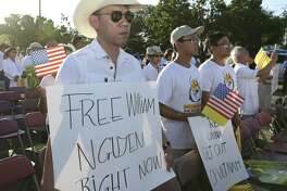 "A Vietnamese American holds a ""Free William Nguyen Right Now"" at a community gathering at Hong Kong City Mall to speak against Vietnamese government leasing three islands to China for 99 years and a candlelight prayer for the people in Vietnam on Wednesday, June 13, 2018, in Houston."