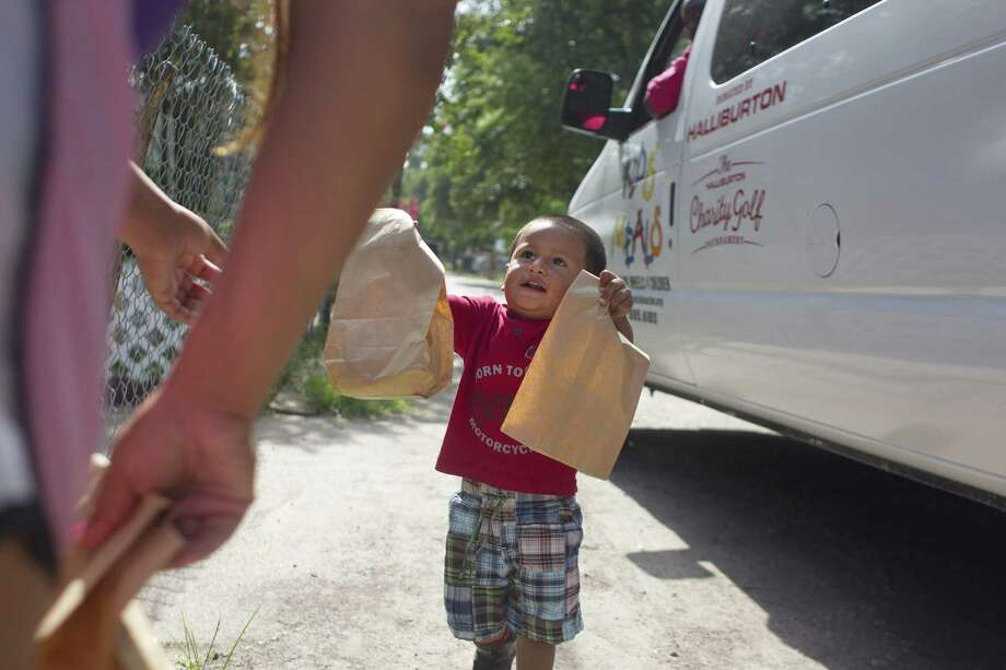 In 2013, an 18-month-old hands his mother prepared lunches for himself and his 4-year-old brother that were delivered from Kids' Meals in Houston. Childhood poverty continues to be a problem throughout Texas, according to the newest KIDS COUNT report. Photo: File Photo /Houston Chronicle / © 2013  Houston Chronicle