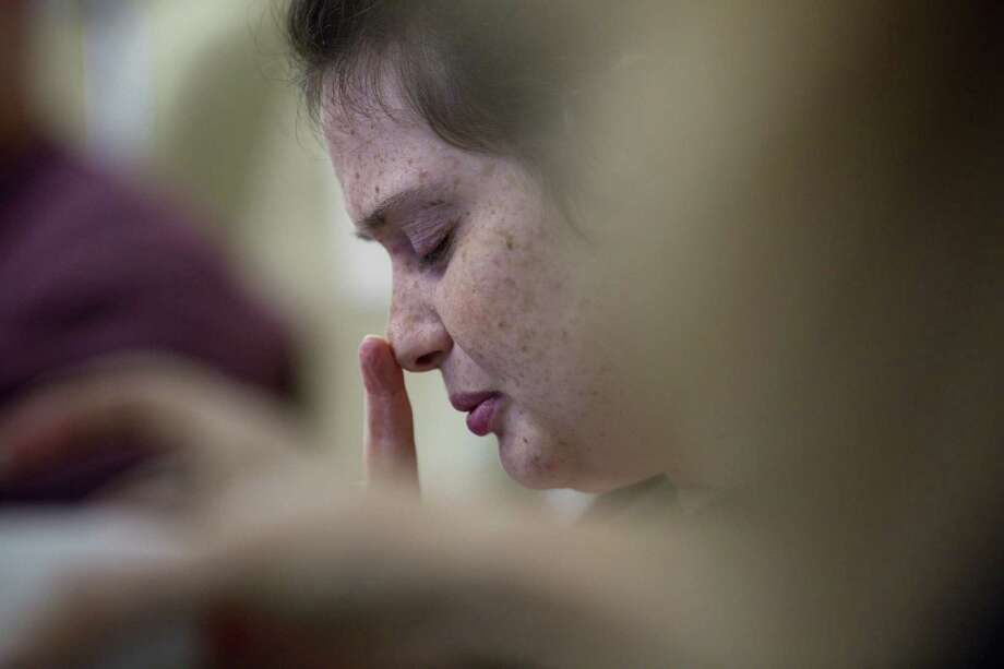 Tiffany Baker touches her nose as she talks to voices in her head, during a medical appointment, Monday, April 9, 2018, in Houston. Baker exhibits many of the classic signs and symptoms of schizophrenia, although doctors believe it may be caused by an autoimmune disease. ( Jon Shapley / Houston Chronicle ) Photo: Jon Shapley/Houston Chronicle / © 2018 Houston Chronicle