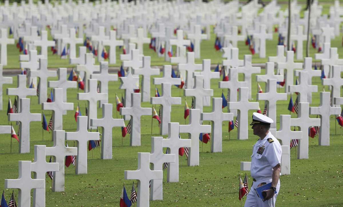 FILE- A U.S. military officer passes by graves of fallen U.S. soldiers at the Manila American Cemetery and Memorial in suburban Taguig, Philippines.