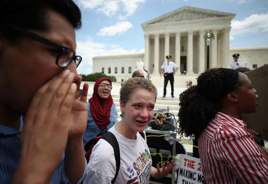 People demonstrate against President Trump's travel ban as protesters gather outside the U.S. Supreme Court following a court issued immigration ruling Tuesday in Washington, D.C. The court issued a 5-4 ruling upholding the president's travel ban imposing limits on travel from several primarily Muslim nations. Photo: Mark Wilson, Staff / Getty Images / 2018 Getty Images