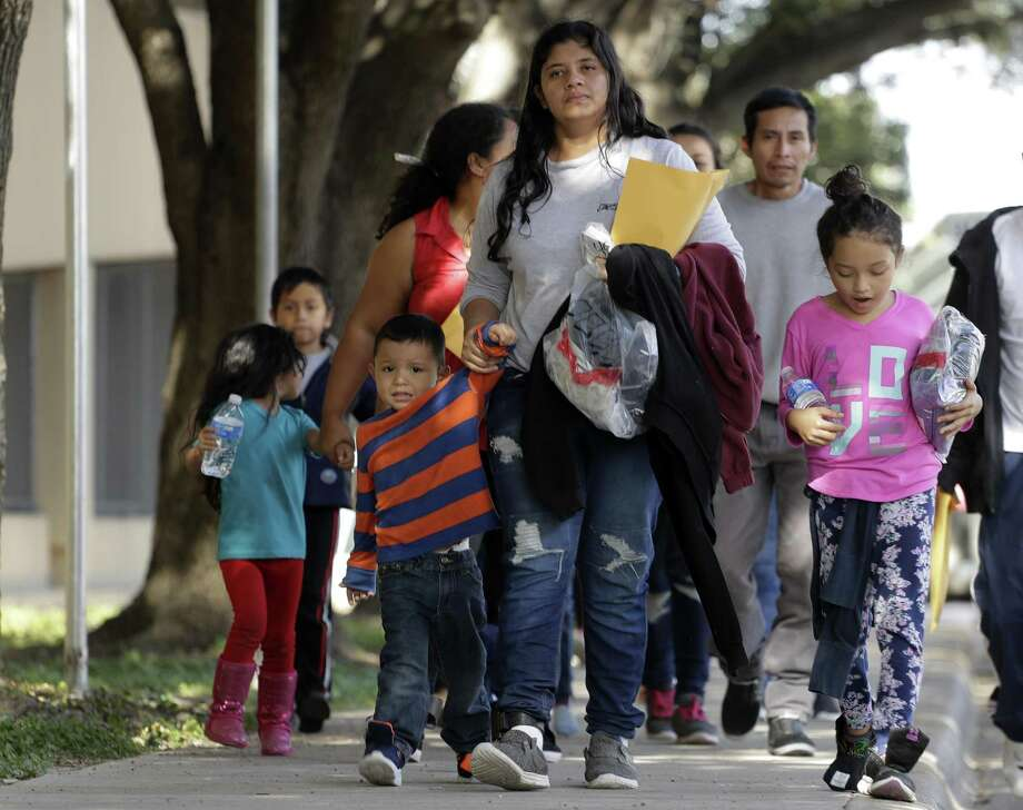 Immigrant families walk to a respite center after they were processed and released by U.S. Customs and Border Protection on Wednesday in McAllen.