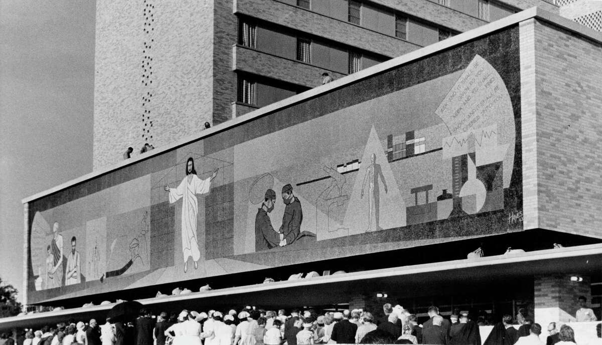 """06/07/1963 - Methodist Hospital formally opened a nine-story, 375-bed addition Thursday to double the size of its facilities. Highlighting the dedication ceremonies was the unveiling of this 95 by 16-foot mosaic tile mural across the front of the new wings fronting Fannin. The mural, presented by Mrs. W. W. Fondren, contains 1.5 million pieces of mosaic tile. Designed by Bruce Hayes of Houston, the mural took more than a year to assemble in Florence, Italy. It is entitled """"The Extending Arms of Christ"""" and shows the interrelation of religion and medicine"""