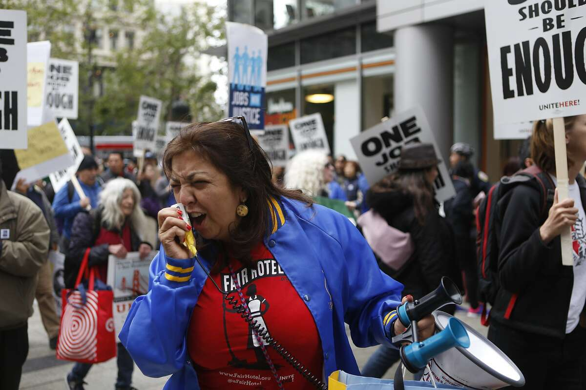A lady yells into a microphone while marching with Unite Here Local 2 on Wednesday, June 27, 2018 in San Francisco, Calif. calling on Marriott to use its leadership in the global hotel industry to create jobs that are enough to live. The march began at both Union Square and Yerba Buena Gardens and culminated at San Francisco Marriott Marquis, the largest Marriott in the city.