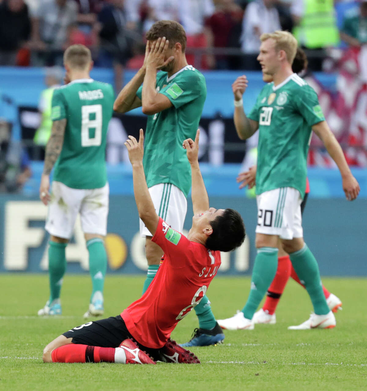 Germany's players walk off the pitch as South Korea's Ju Se-jong, front celebrates after the group F match between South Korea and Germany, at the 2018 soccer World Cup in the Kazan Arena in Kazan, Russia, Wednesday, June 27, 2018. (AP Photo/Lee Jin-man)