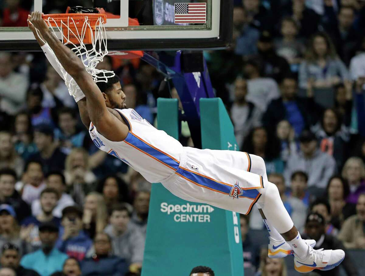 FILE - In this Jan. 13, 2018, file photo, Oklahoma City Thunder's Paul George (13) hangs from the rim after a dunk against the Charlotte Hornets during the first half of an NBA basketball game in Charlotte, N.C. An NBA free-agent class with a little something for everyone hits the market on July 1. The group includes an array of superstars, big men, glue guys and sharp-shooters. (AP Photo/Chuck Burton, File)
