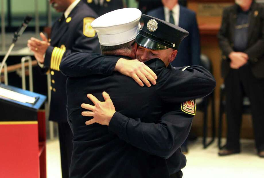 Ryan Sullivan, facing camera, receives a hug from his father, retired Fairfield firefighter Lt. Michael Sullivan, after graduating with Recruit Class #61 during Bridgeport Fire Department's Promotional and Swearing in Ceremony at Common Council Chambers at Bridgeport City Hall in Bridgeport, Conn., on Wednesday June 27, 2018. Ryan will be a fourth generation firefighter in his family. Photo: Christian Abraham / Hearst Connecticut Media / Connecticut Post