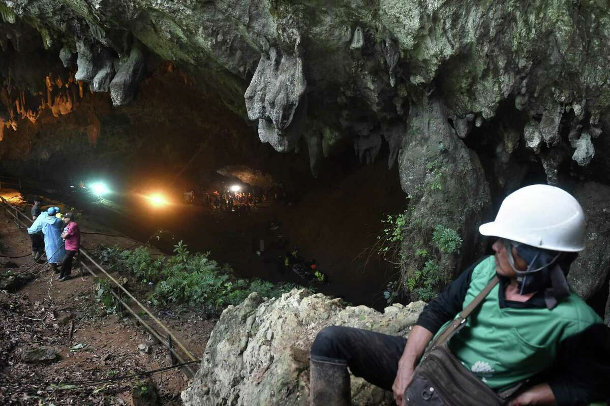 TOPSHOT - Rescue personnel are seen at the opening of the Tham Luang cave in Khun Nam Nang Non Forest Park in Chiang Rai on June 27, 2018 while operation continue for a missing children's football team and their coach. The desperate search for 12 children and their football coach trapped since June 23 in a flooded cave in northern Thailand pressed on as distraught relatives prayed and awaited news about the missing youngsters. / AFP PHOTO / LILLIAN SUWANRUMPHALILLIAN SUWANRUMPHA/AFP/Getty Images