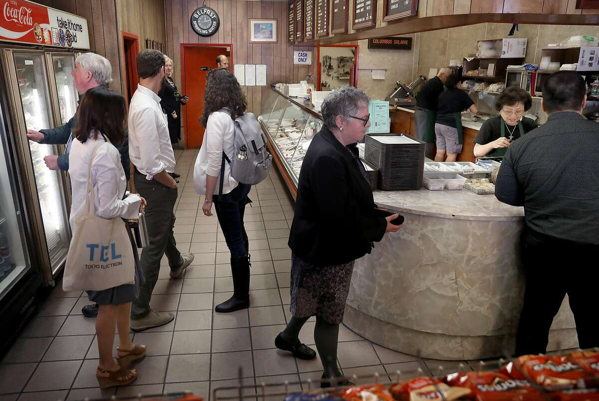 Jean Aburahma (right, behind counter) rings up customers during lunch time at Turk & Larkin Deli on Monday, June 25, 2018, in San Francisco, Calif.