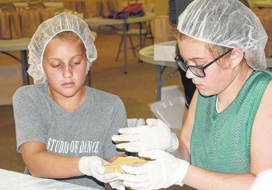Megan Marshall (left), 10, and Karsyn Mudd, 11, help make sandwiches for the Summer Lunch Program Wednesday at Grace United Methodist Church. Photo:       Samantha McDaniel-Ogletree   Journal-Courier