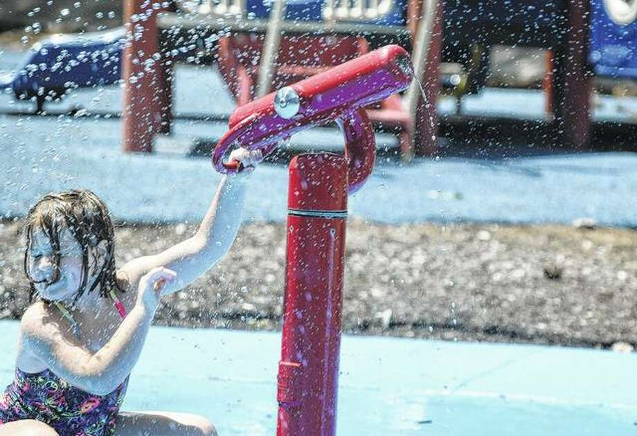 Nora Shaw, 6, the daughter of Ryan and Maryon Shaw of Bluffs, plays on the splash pad at Godfrey Park on Wednesday. Photo:       Samantha McDaniel-Ogletree | Journal-Courier