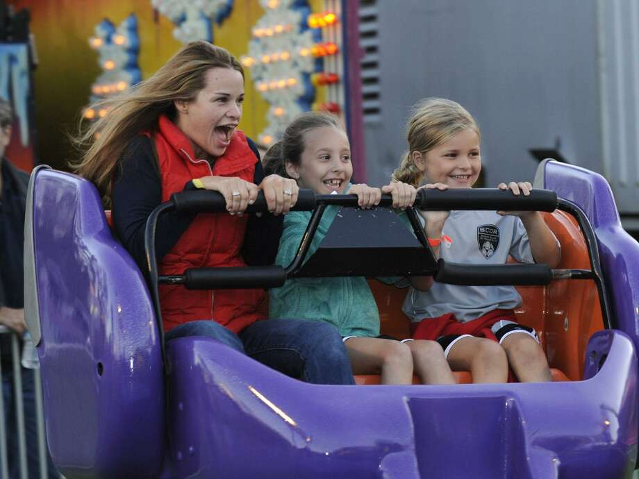 Taking a ride on the Sizzler at the Ridgefield Chamber of Commerce community carnival are from left, Christie Thompson, of Ridgefield, Brooke Elliott, 7, and Callie Thompson, 7, Friday, Sept. 21, 2012. Photo: Carol Kaliff / Carol Kaliff / The News-Times
