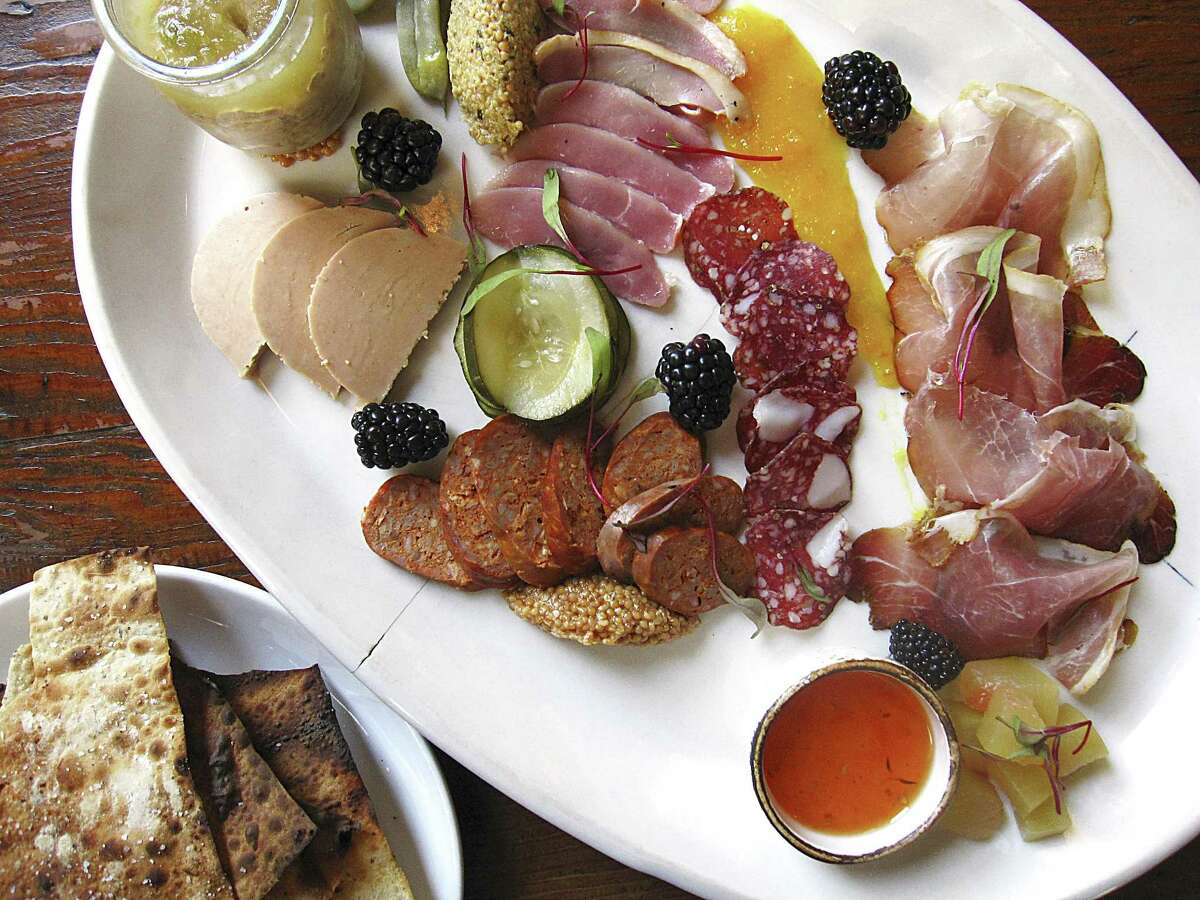 Charcuterie plate with foie gras, apple-jalapeño pork rillette, duck ham, lamb-and-fennel salami, lamb chorizo and 9-month speck with beer crackers, jams and mustards from Cured.