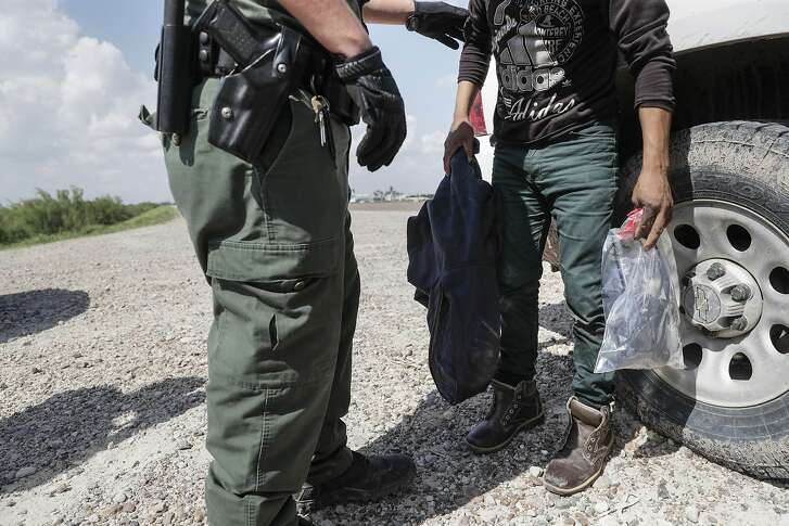 Border patrol agent Rene Cisneros frisks Gerberht Carac, 19, of Guatamala, who was apprehended while attempting to illegally cross the U.S./Mexico border on June 25, 2018 near McAllen, Texas. Detainees must remove shoelaces, belts and other items, putting them into a plastic bag.  (Robert Gauthier/Los Angeles Times/TNS)