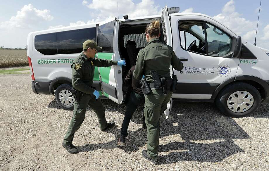 U.S. Border Patrol agents load a migrant from Guatemala into a van after he was caught trying to enter the United States illegally, Monday, June 25, 2018, in Hidalgo, Texas. (AP Photo/David J. Phillip) Photo: David J. Phillip, Associated Press
