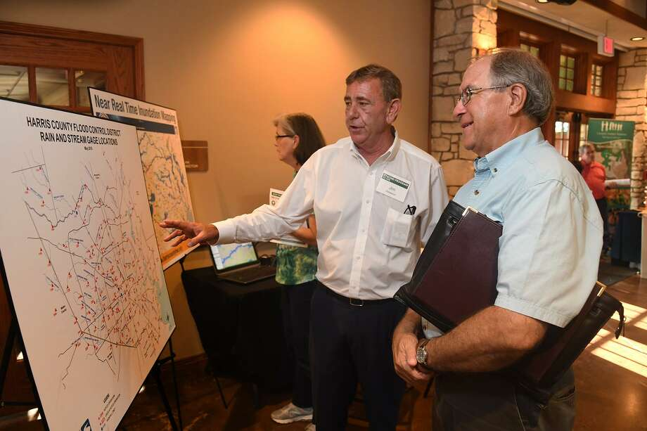 Jim Greeson, a Harris County Flood Control District Professional Engineer, chats about the HCFCD Rain & Stream Gage Location Map with Jim Robetson, Chairman of the Cypress Creek Flood Control Coalition during the Harris County Flood Control District flood mitigation bond program meeting for Spring Creek watershed in June. The meeting for the Little Cypress Creek watershed was held Tuesday at the Richard and Meg Weekley Community Center at 8440 Greenhouse Road in Cypress. Projects were discussed for both Little Cypress Creek and Cypress Creek watersheds.(Jerry Baker/For the Chronicle) Photo: Jerry Baker, Freelance / For The Chronicle / Freelance