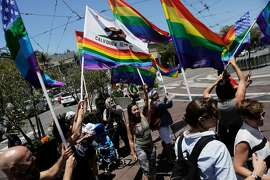 A group of people wave rainbow flags on Castro Street in celebration of the news of the Supreme Court's decision to recognize the 14th Amendment's requirement to license marriages between two people of the same sex in San Francisco on Friday, June 26, 2015.