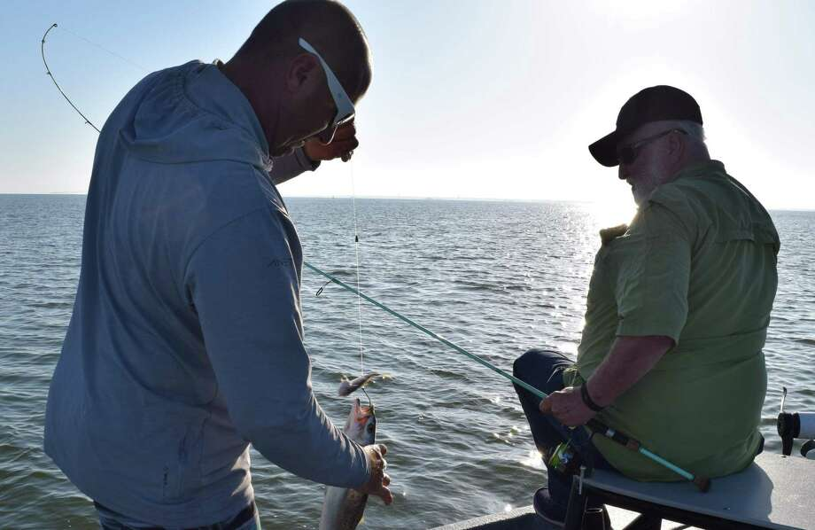 This keeper trout landed by Harvey Winingham of Phoenix hit a croaker with authority -- note the bait is on the line above the hook being removed by Capt. Joey Farah before the keeper trout is placed in a cooler for the trip back to the dock. Photo: Ralph Wininngham /For The Express-News